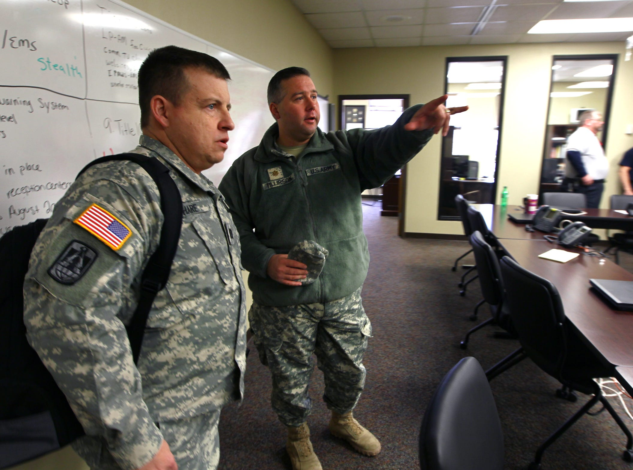 Capt. Brian Hare, left, 228th Signal Brigade of Spartanburg, listens to Maj. Brian Tillirson, 263rd Army Air and Missle Defense Command, at the Anderson County Emergency Operations Center in Anderson in 2014.