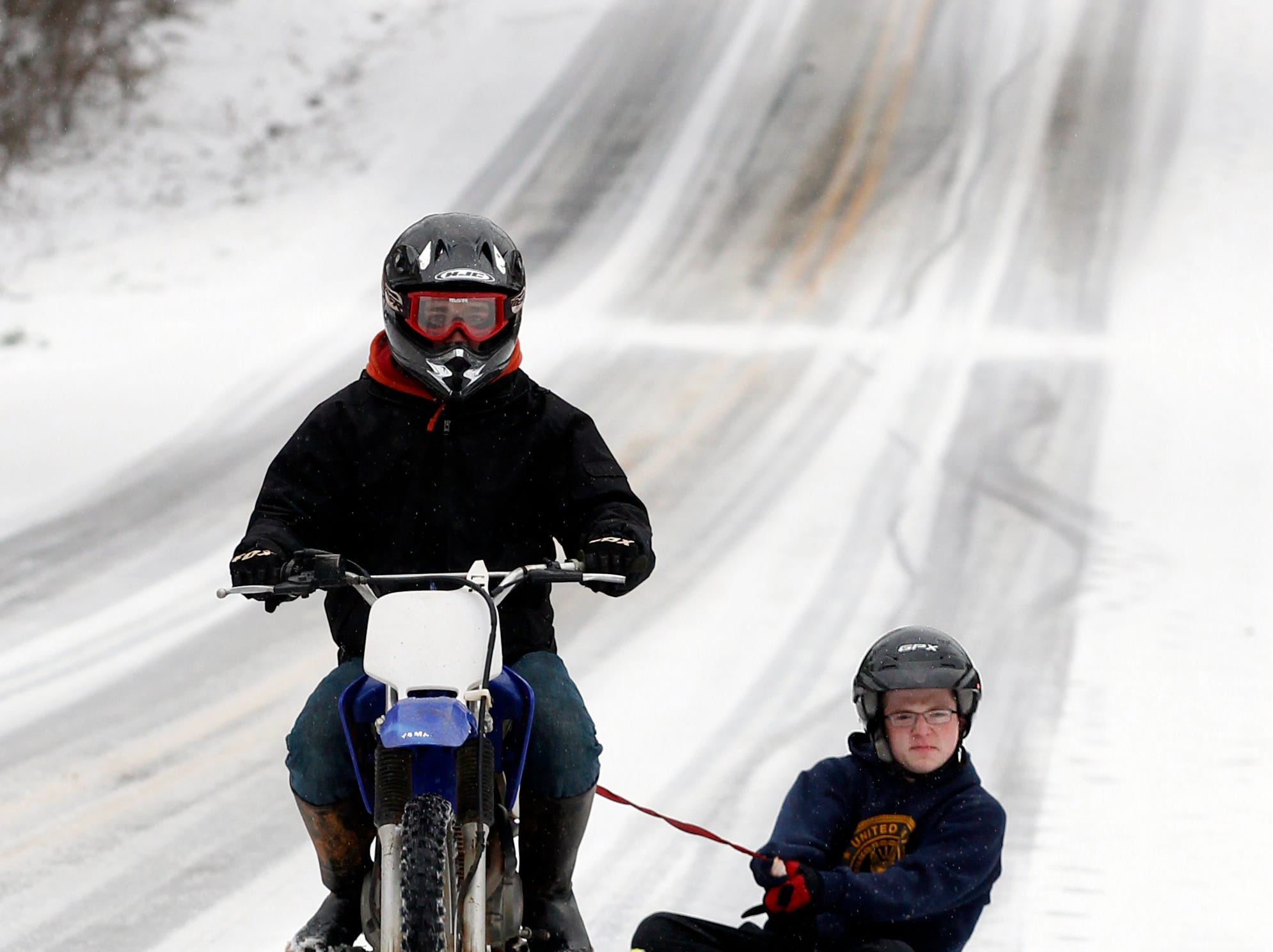 Conner Ferguson uses a dirt bike to pull Bryce Blair on a sled along Calhoun Street in Anderson on Wednesday February 12, 2014.