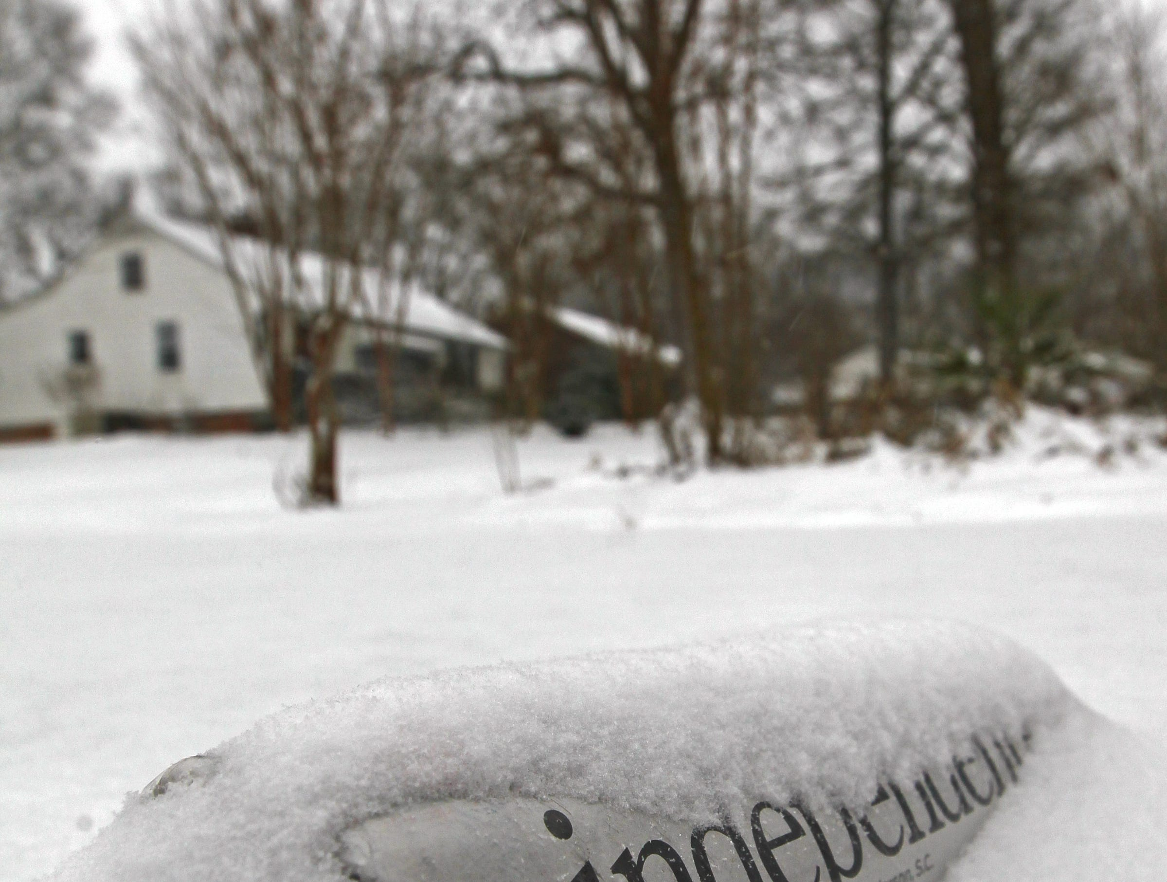 An Anderson Independent Mail newspaper, wrapped in a plastic bag, is partly covered in snow in a driveway in Anderson during the first snow of 2014.