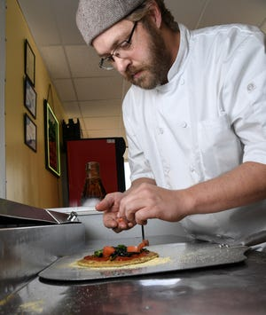 Bandits Pizzeria general manager Leland Tucker makes a pizza at 4118 Clemson Boulevard in Anderson.
