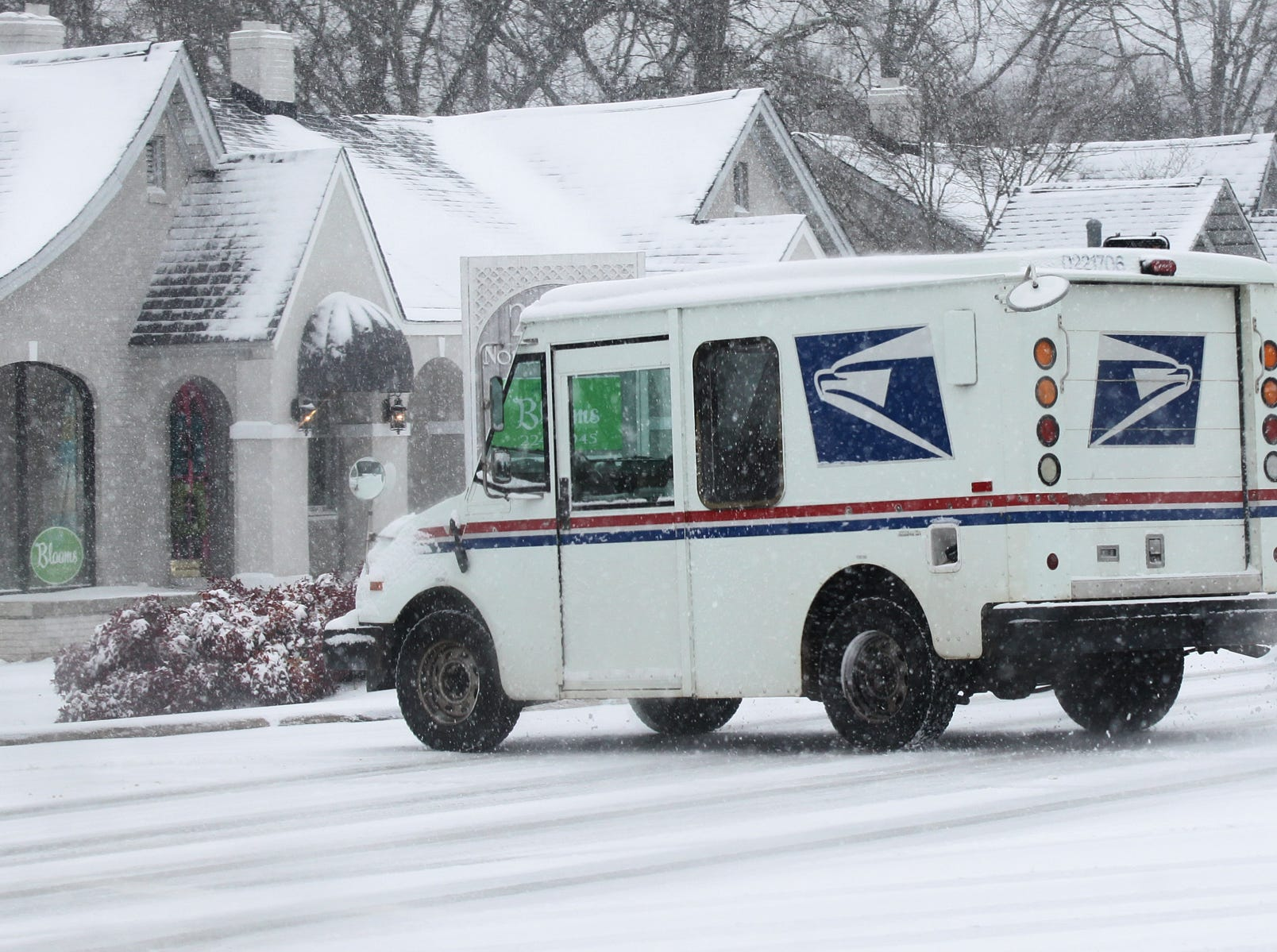 A United States Postal Service vehicle turns into a business to deliver mail in Anderson during the first snow of 2014.