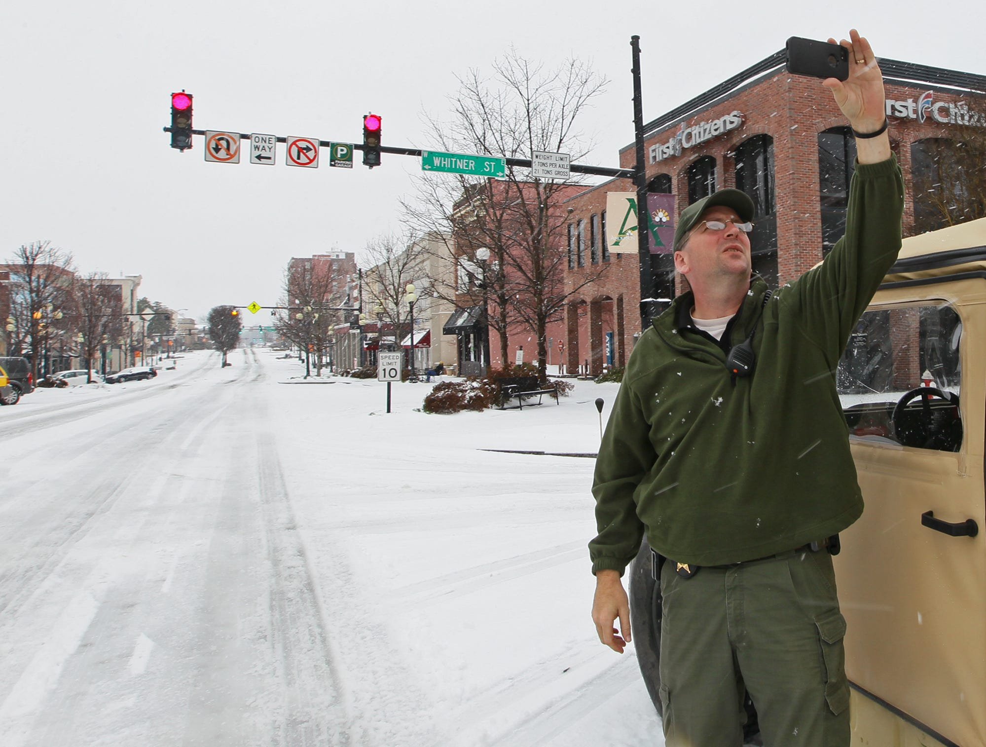 Capt. Matthew Littleton, deputy emergency manager of Anderson County Emergency Services, documents snow conditions in downtown Anderson in 2014.