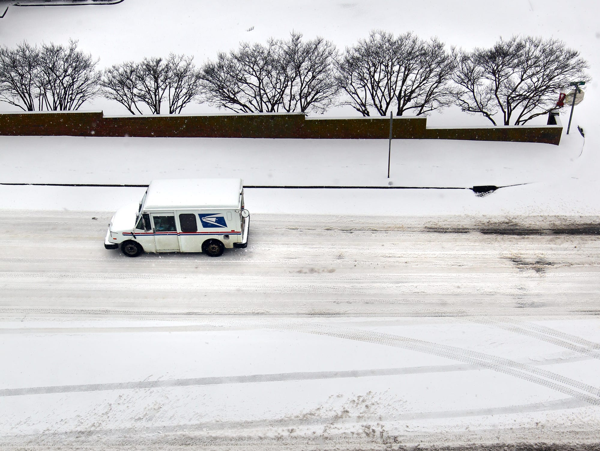 A United States Postal truck drives through the melting snow on Murray Avenue in Anderson. The sun and warmer temperatures started melting the snow, and vehicles made and followed tracks during the first snow of 2014.