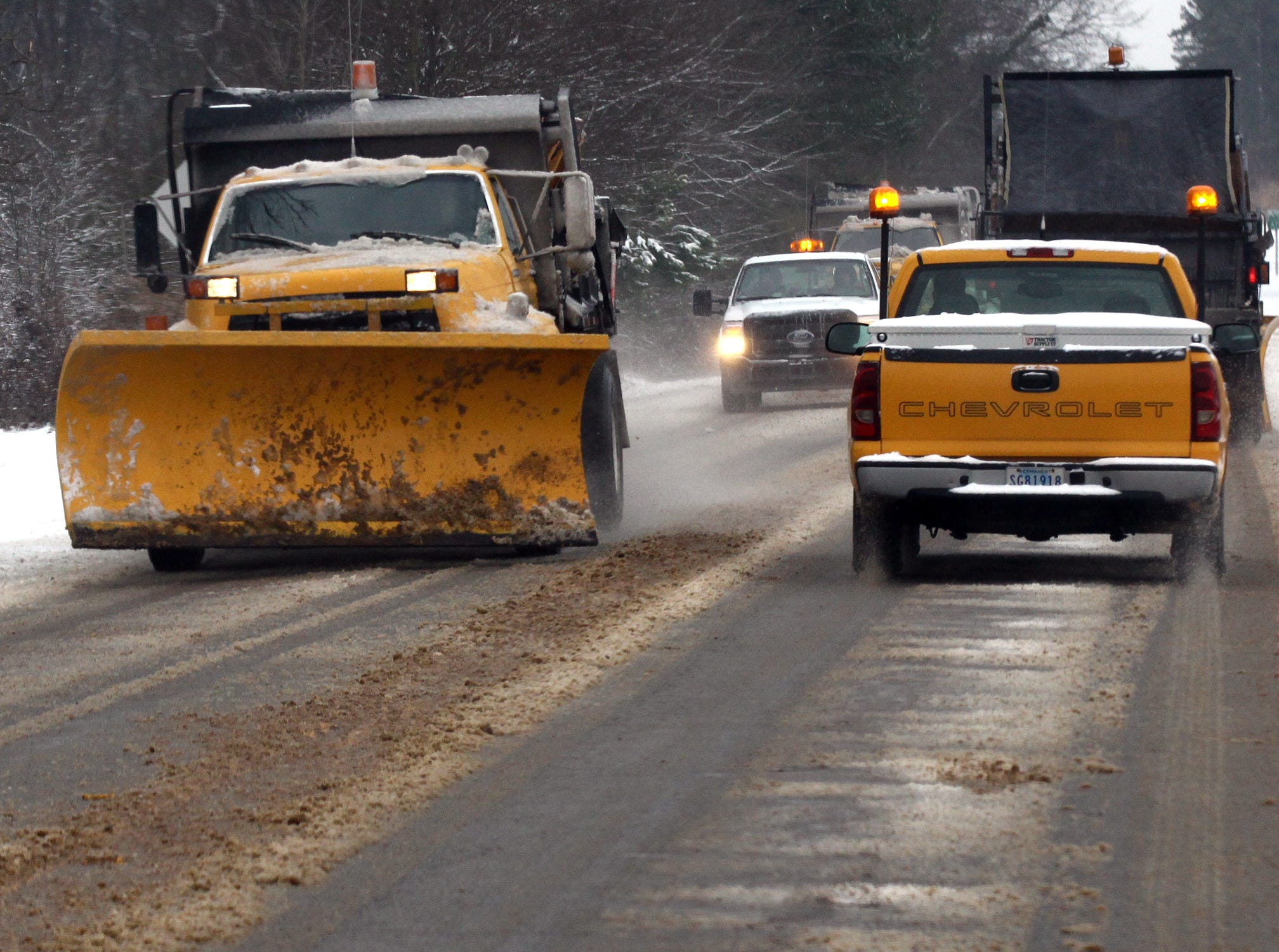 Sand trucks pass each other near the South Carolina Department of Transportation center on S.C. 178 in Anderson during the first snow of 2014.