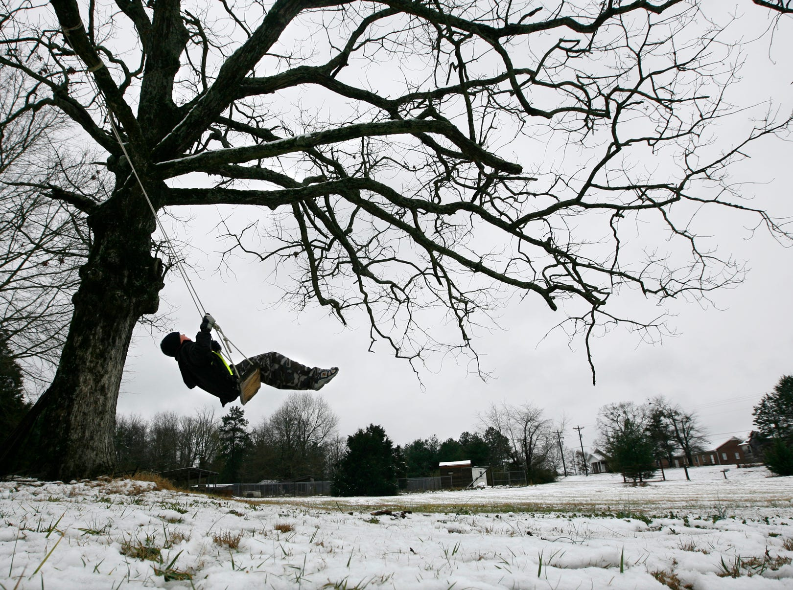 Ethan King, 12, of Townville swings in his front yard Thursday after a storm left the area with a blanket of white snow.   Many children and adults could spend time in the snow since area schools cancelled classes for the day in 2008.