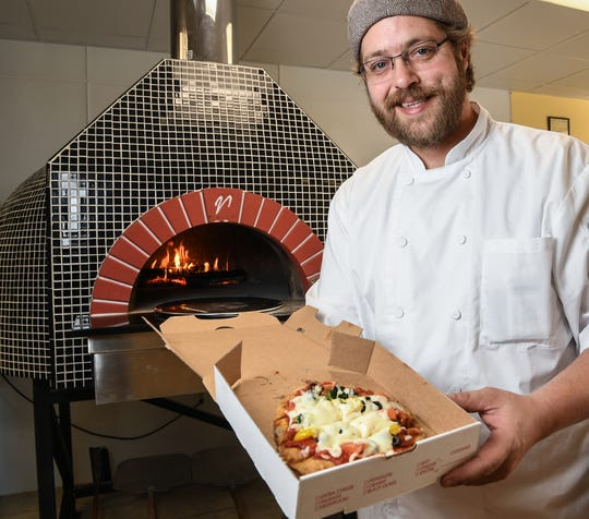 Bandits Pizzeria general manager Leland Tucker holds a personal size veggie pizza next to a stone oven, at 4118 Clemson Boulevard in Anderson.