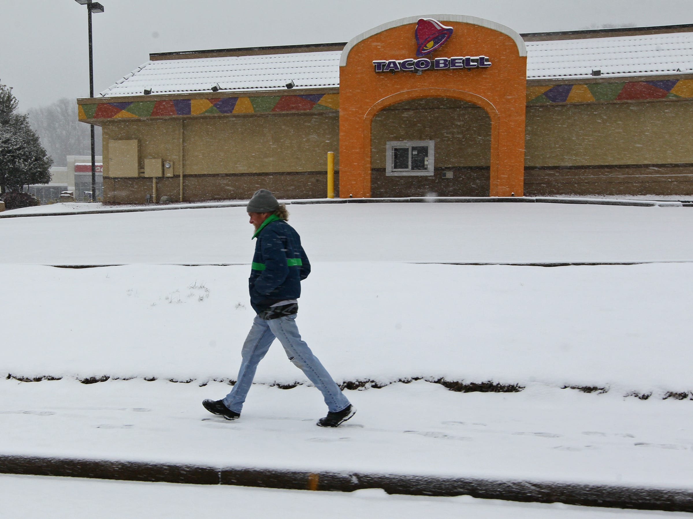 A man walks by a Taco Bell on Clemson Boulevard, one of several businesses closed due to the snow storm in Anderson during the first snow of 2014.