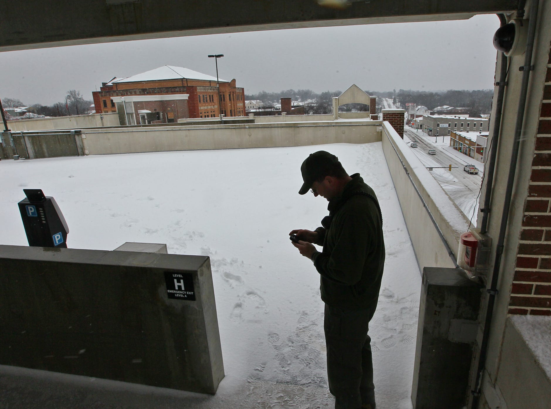 Capt. Matthew Littleton, technical services division of the Anderson County Emergency Operations Center, Tweets a status of the snow storm from the top of the Anderson parking garageduring the first snow of 2014.