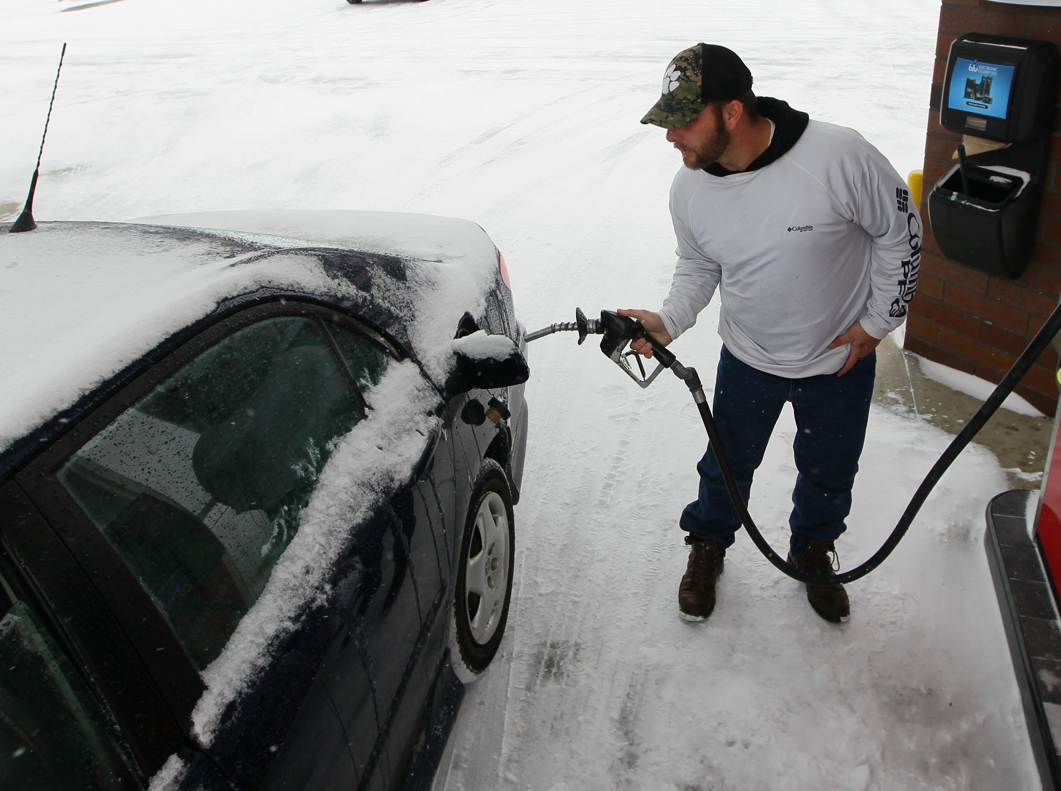 Brandon Eskew of Anderson puts gas in his car at the QT on S.C. 28 Bypass in Anderson during the first snow of 2014.