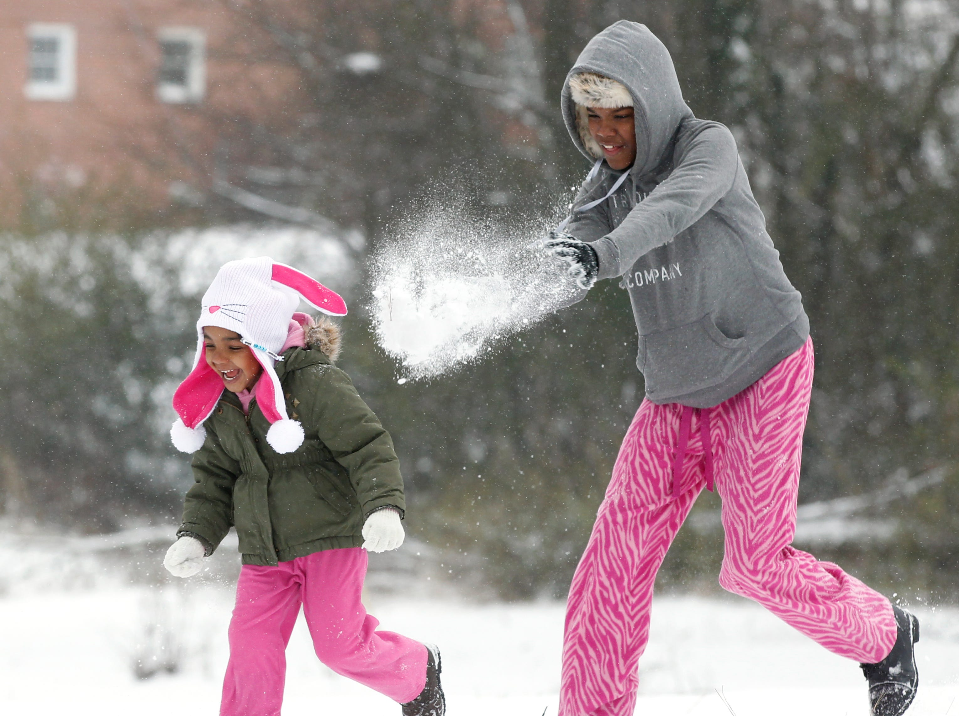 Xyiera Jenkins, right, hits her sister Johnecia Wiley with a snowball in the front yard of their Anderson home on Wednesday February 12, 2014.