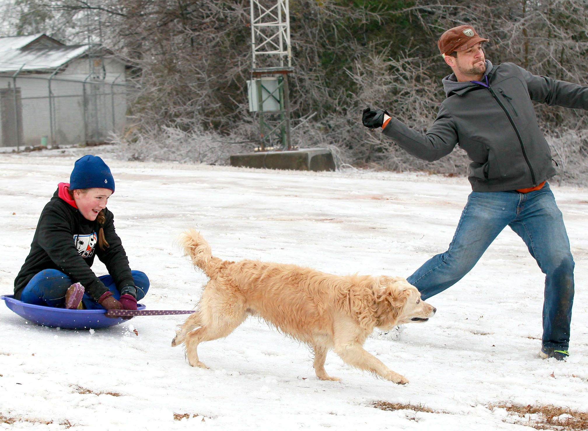 Tommi Roberts, left, holds a leash with Jaxson, a retriever mix, while her father throws a stick, to help pull her down the snow-covered Kite Hill, near U.S. 76 in Clemson in 2015.