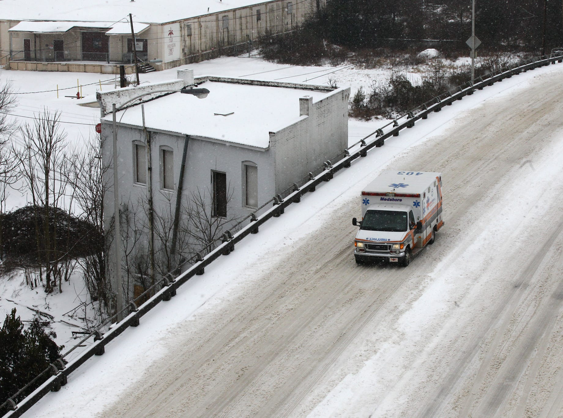 An ambulance drives on Murray Avenue in Anderson, over a bridge covered with snowduring the first snow of 2014.