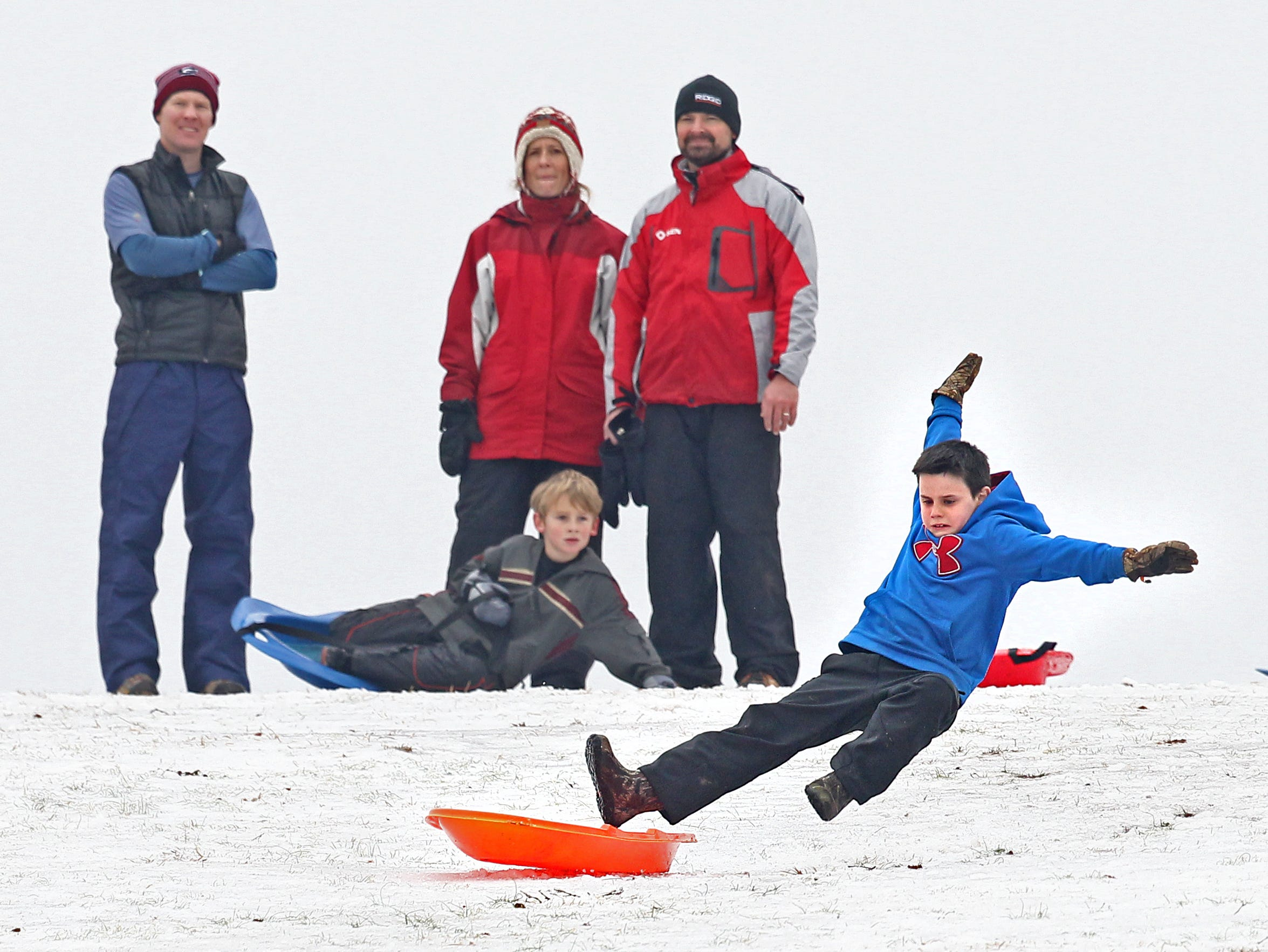 Cannon Tyson, right, of Pendleton, slips after sliding down part of a snow-covered Kite Hill off of U.S. 76 in Clemson. The semi-soft snow made for a soft landing, but slick enough to get some good movement down the hill in 2015.