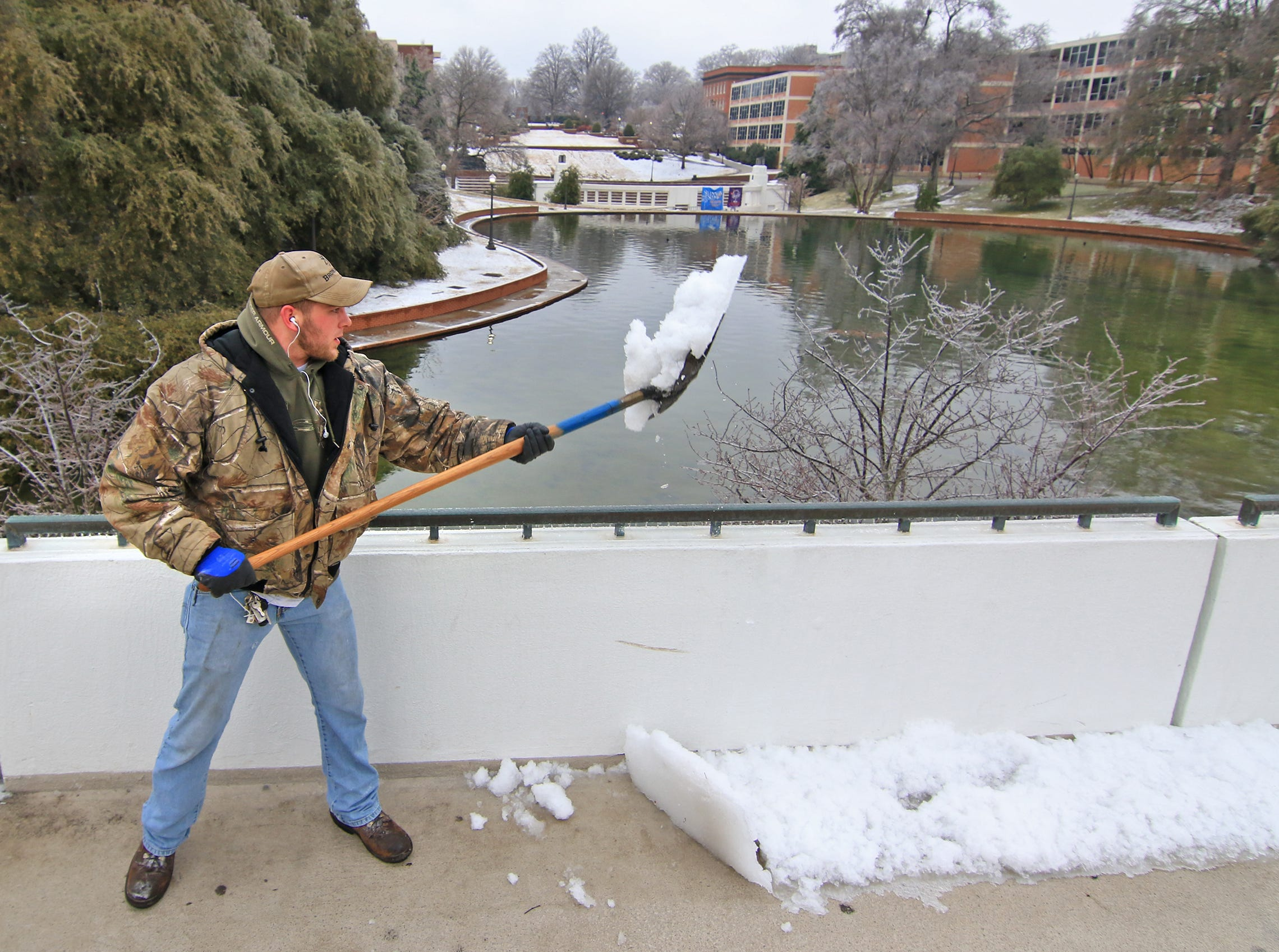 James Stewart of Clemson University grounds crew shovels snow off the bridge in front of Cooper Library. Classes resumed at 12:30 p.m. Tuesday after a weather delay in 2015.