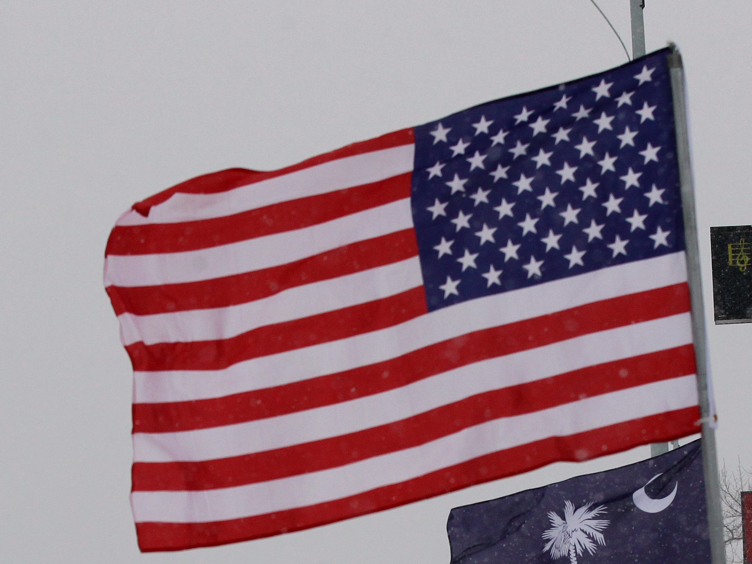A car drives by flags blowing in the wind and snow on North Main Street in Anderson during the first snow of 2014.