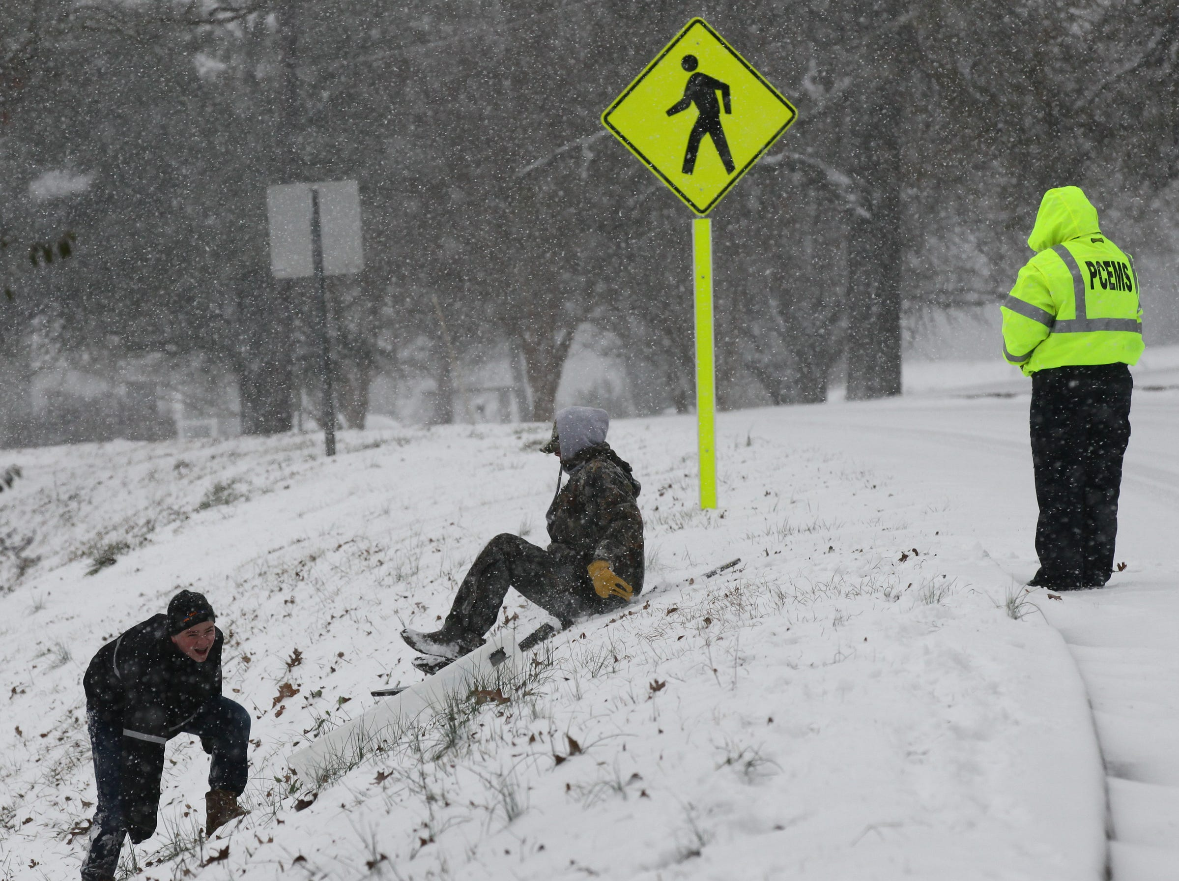 Residents slide down an embankment on cardboard during the first snow of 2014.