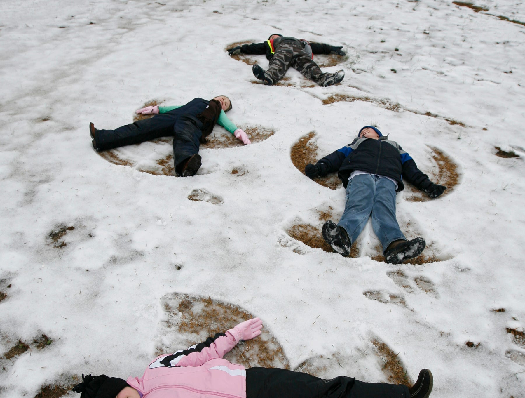 Emily Roesch, below, 10, of Townville makes snow angles with her sister Hannah Roesch, left, 7, neighbors Ethan King, top, 12, and Luke McIntire, right, 10, Thursday morning in Townville in 2008.