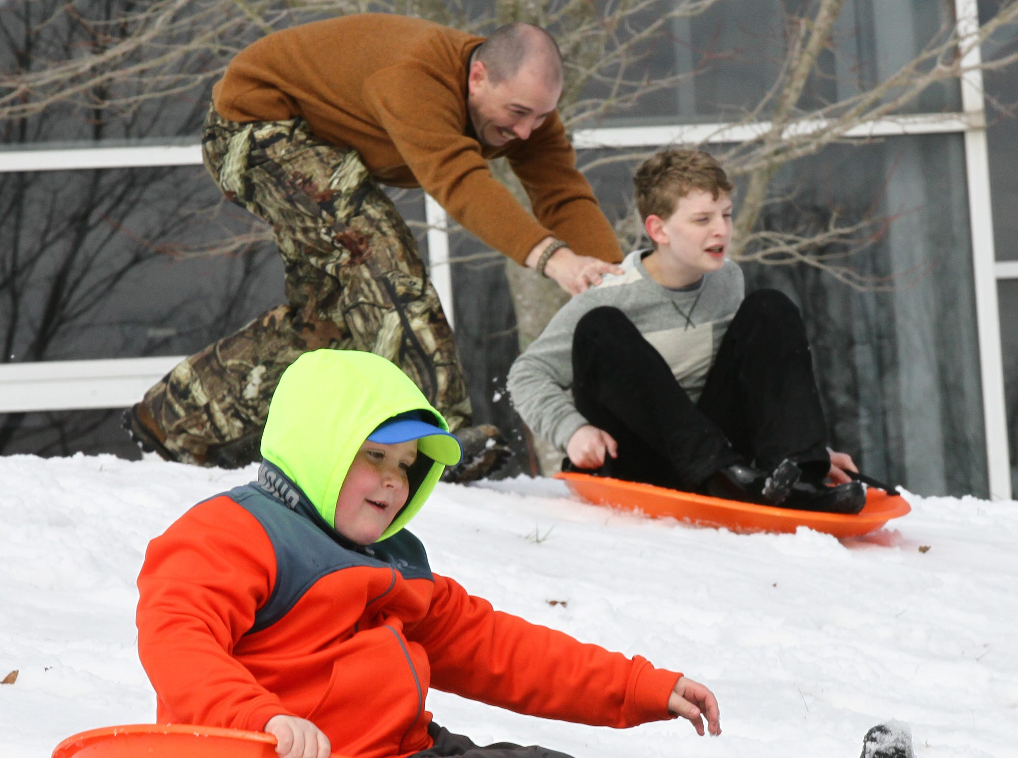 Colton Gaines, left, and Hunter Crowe, right, slide down a hill covered with snow at the Civic Center of Anderson in 2014.