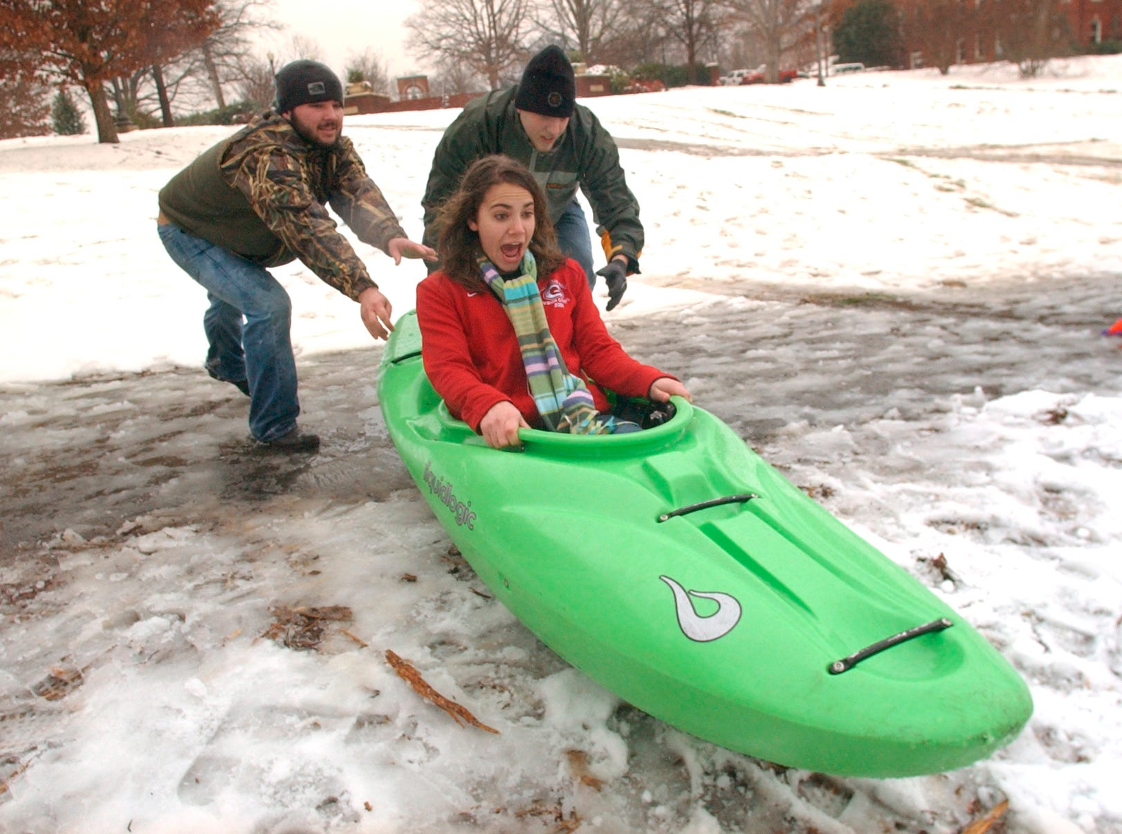 Clemson University freshman Lindsay Stewart, 18, middle, of Greenville, S.C. gets a push in a kayak from fellow freshmen Mason Sanders, left, 19, of Anderson, S.C., and Andy Jordan, right, 19, of Anderson, S.C. Thursday February 1, 2007 on a hill in Clemson, S.C.