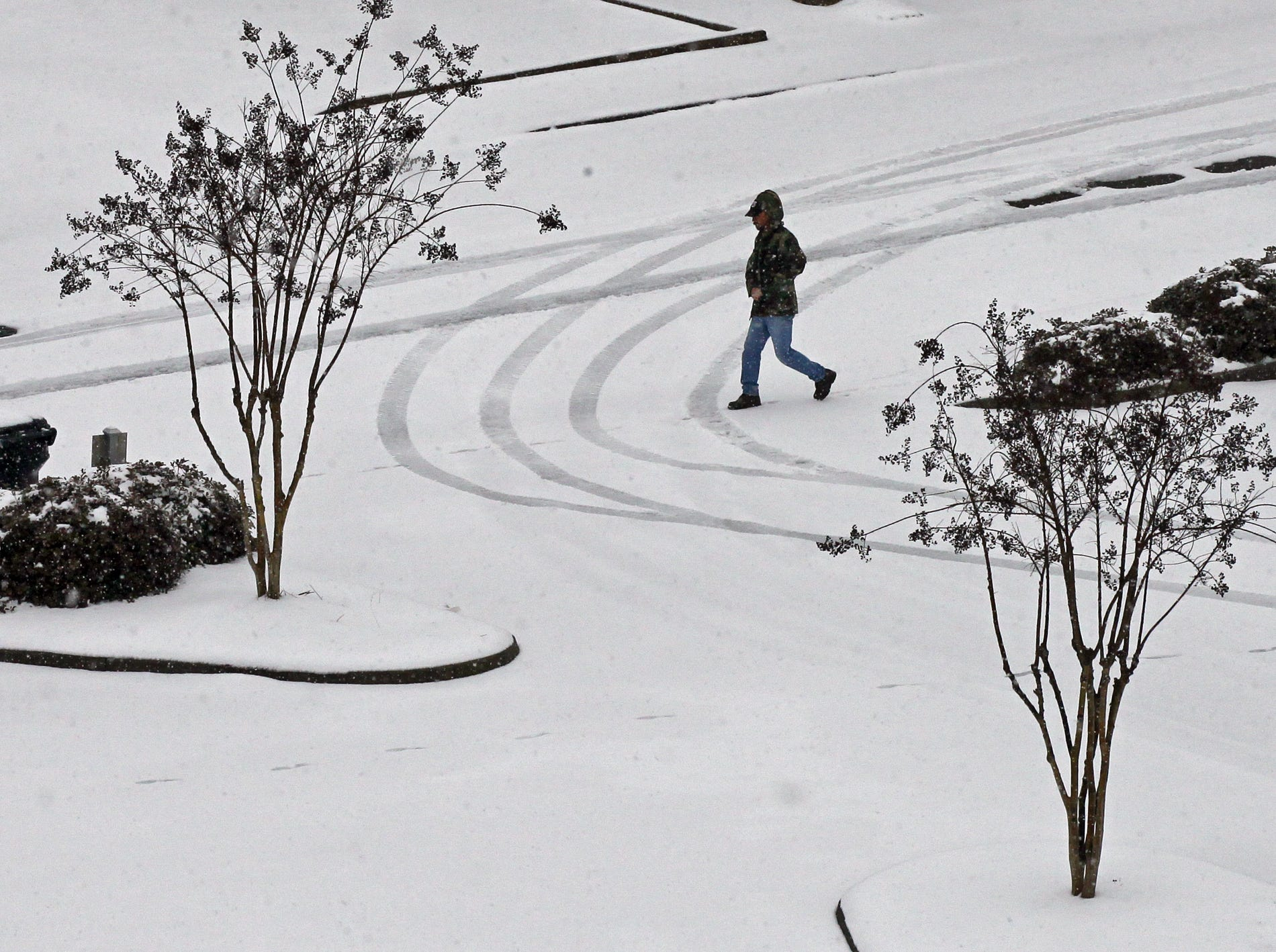A man walks through snow on West Orr Street in Anderson during the first snow of 2014.