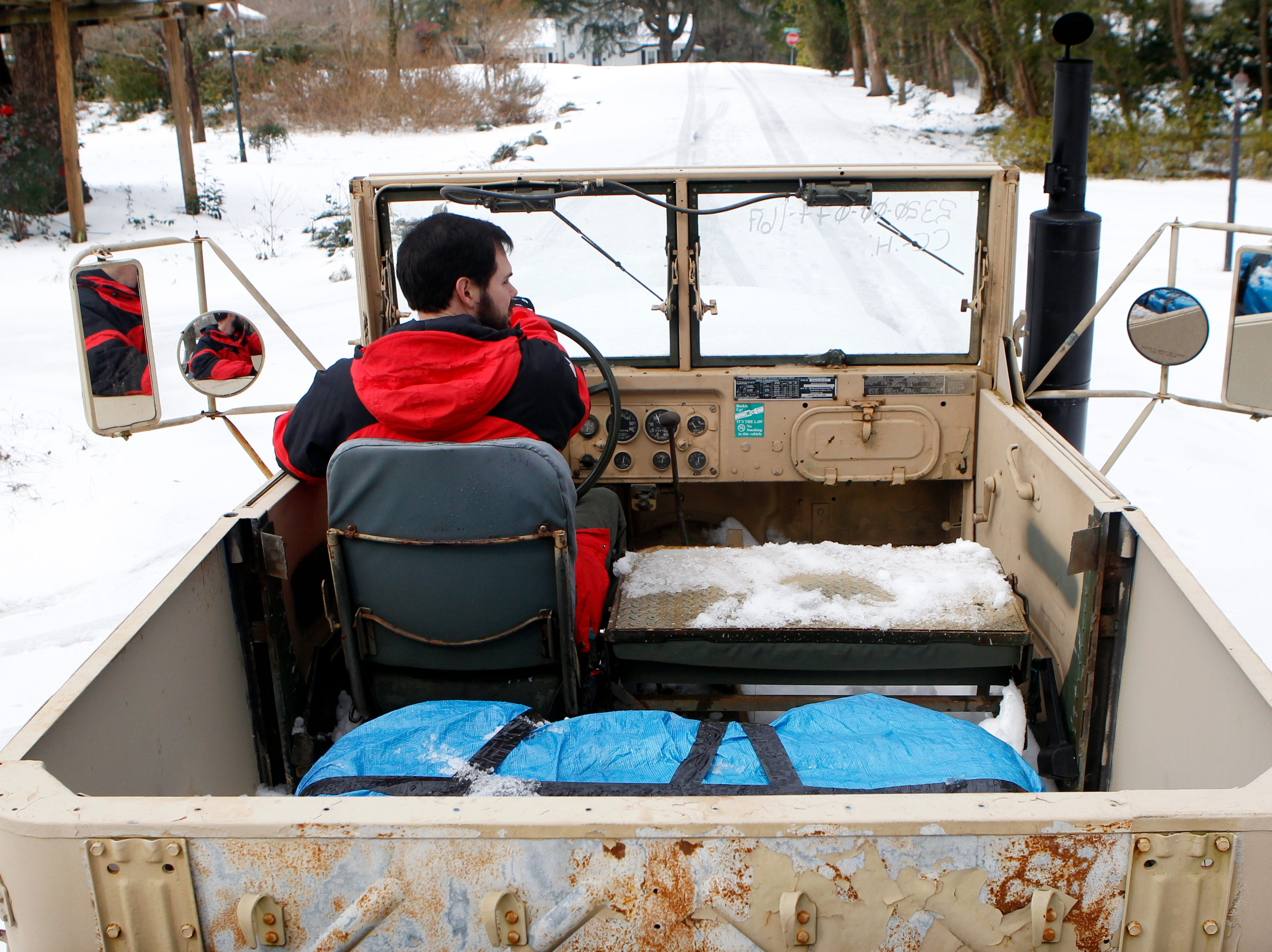 """Weston Rainey drives his 13,500-lb. 1970 M35A2 U.S. Army truck, better known as a """"Deuce and a Half"""", to break up the snow and ice on the streets of his Anderson neighborhood on Thursday February 13, 2014."""