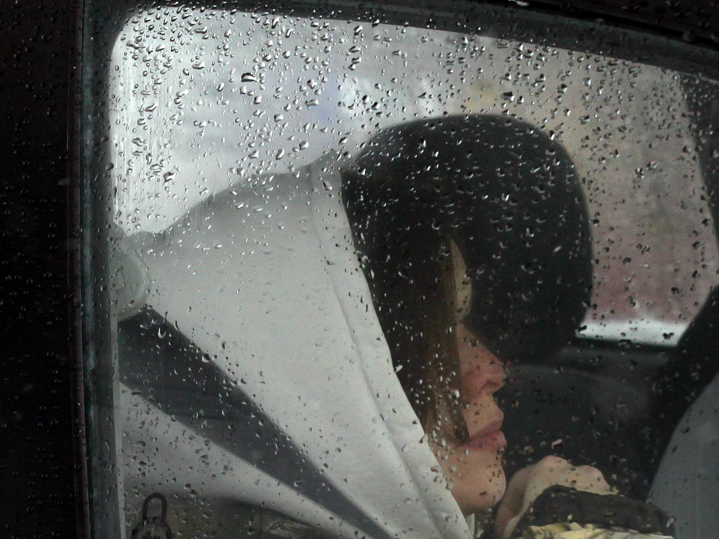 Tonya Eskew of Anderson bundles up in a vehicle her husband Brandon Eskew drove around for some necessities, including gas for the car during the first snow of 2014.