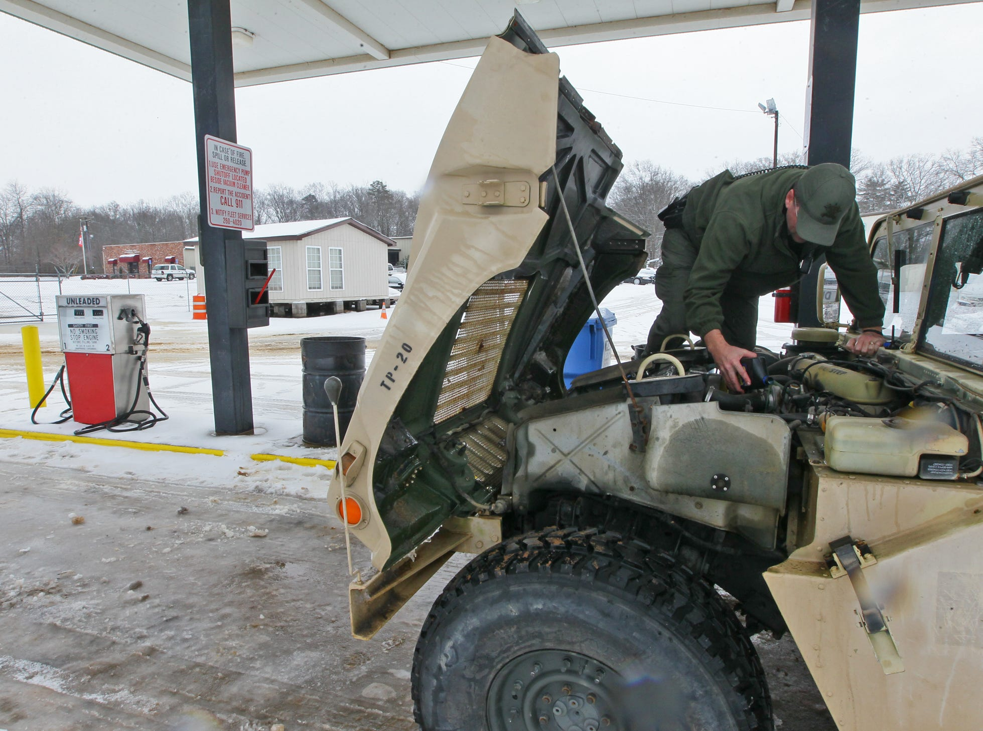 Capt Matthew Littleton, deputy emergency manager of Anderson County Emergency Services, checks transmission fluid levels on a Humvee with four-wheel drive, at the county road maintenance facility in Andersonduring the first snow of 2014.