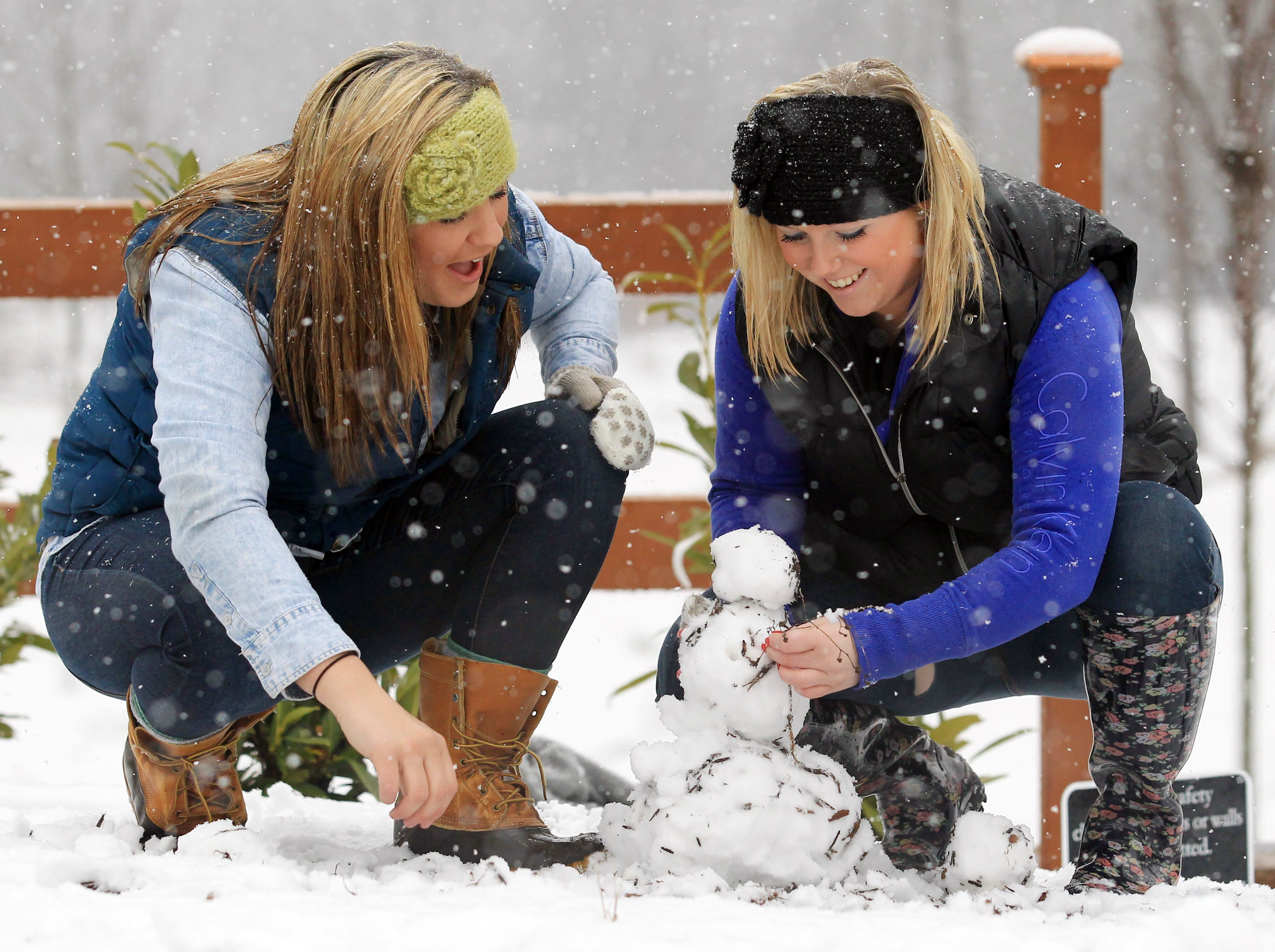 Anderson University students Madison Smith, right, of Powdersville, and Remi Jordan, of Anderson, make a small snowman in Linley Park on Tuesday February 11, 2014.