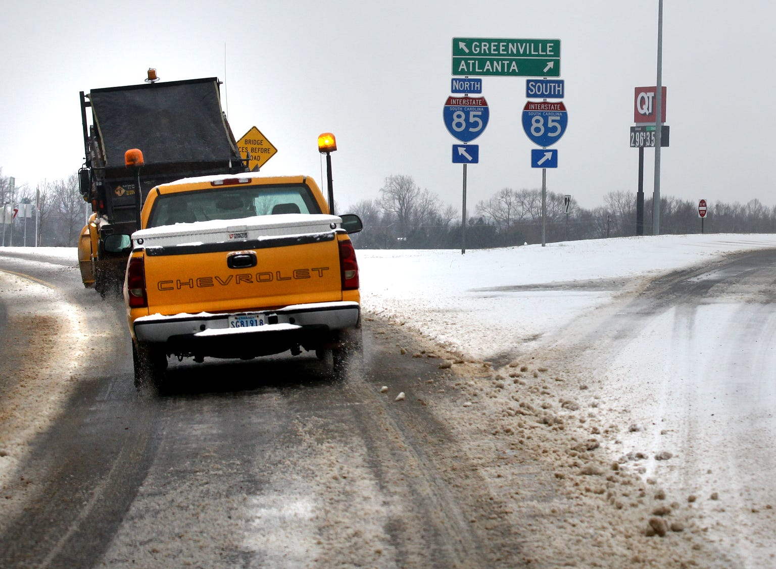 A sand truck from the South Carolina Department of Transportation center drives along S.C. 178 in Anderson, passing an I-85 exit ramp during the first snow of 2014.