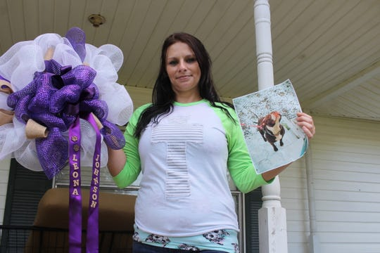 Monica Renee Johnson holds a wreath she made to remember her dog, Leona (right), which had been killed just days before in June as a warrant was served by the Rapides Parish Sheriff's Office at her Forest Hill home. Johnson was arrested during that incident, and she was arrested again Tuesday on more drug-related charges.