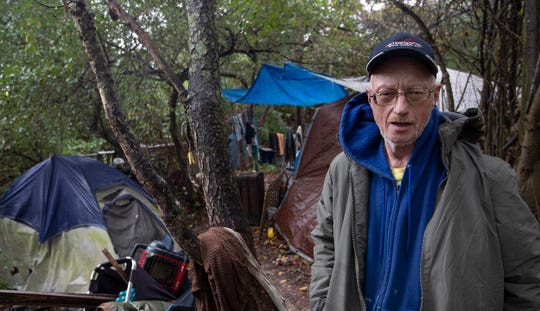 "Homeless resident ""Joe"" outside his tent as he prepares to head out to work for the day."