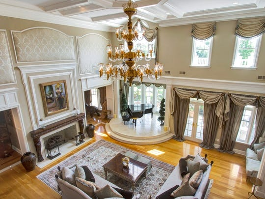 The great room features two-story with balcony overlooks limestone piano pedestal with a two-sided fish tank arched doorways.