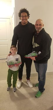 New England Patriots lineman Derek Rivers (center) with Jamesy Raffone and dad Jim Raffone and the JAR of Hope cleats.