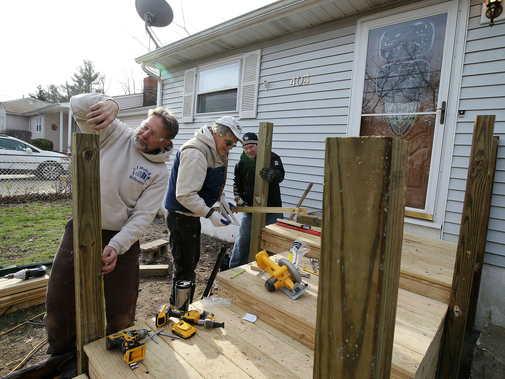 Bob Conway of Whiting, construction supervisor for Northern Ocean Habitat for Humanity, Jeff Dickert of New Egypt, volunteer for Northern Ocean Habitat for Humanity, and Jason Barger of Point Pleasant Boro, outside sales representative for Ferguson Enterprises, work on the home of Korean War veteran Walter Brandon, 85, and wife Patricia, which is Northern Ocean Habitat for Humanity's 200th home repair, in Brick, NJ Thursday, December 6, 2018.