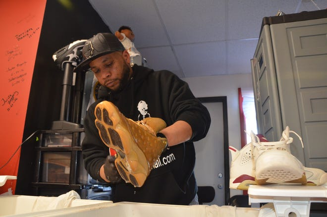 Dr Shoes owner Kevin Jones cleans shoes for $5 a pair with a cleaner that he developed himself. He cleans about 200 pairs a month.
