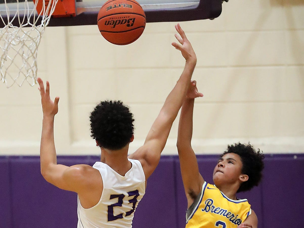 Bremerton's Joseph C. Wilson (3) fouls North Kitsap's Shaa Humphrey (23) as he tries to block the shot during their game in Poulsbo on Wednesday, December 5, 2018.