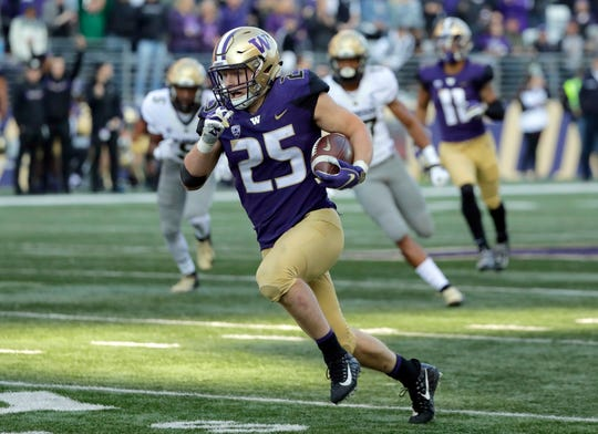 In this Oct. 20, 2018, file photo, Washington linebacker Ben Burr-Kirven (25) runs after he intercepted a pass thrown by Colorado quarterback Steven Montez during the second half of an NCAA college football game in Seattle. Burr-Kirven was named the Pac-12 defensive player of the year Thursday, Dec. 6, 2018.