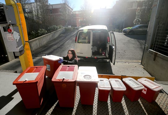 Lisa Al-Hakim director of operations of the People's Harm Reduction Alliance unloads used syringes onto loading dock at the Norm Dicks Government Center on Thursday, December, 6, 2018.