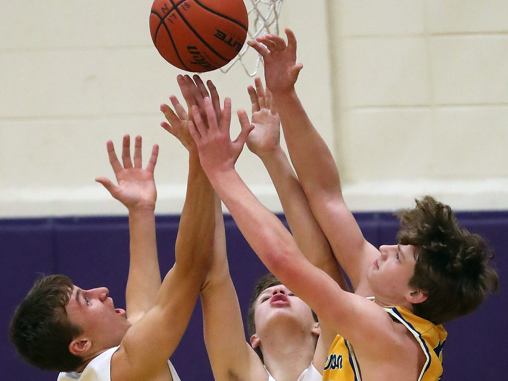 North Kitsap's Logan Chmielewski (21), Bobby Seibers (10) and Bremerton's Kaleb Peterson make a grab for a rebound during the first half of their game in Poulsbo on Wednesday, December 5, 2018.