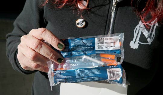 Lisa Al-Hakim, director of operations of the People's Harm Reduction Alliance, holds a package of new syringes last month. The Kitsap Public Health Board approved a six-month extension of its contract with the alliance to provide mobile syringe exchange services, despite reservations on the part of some board members.