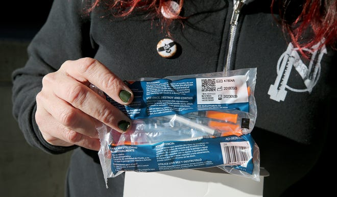 Lisa Al-Hakim, director of operations of the People's Harm Reduction Alliance, holds a package of new syringes on Thursday, December, 6, 2018.