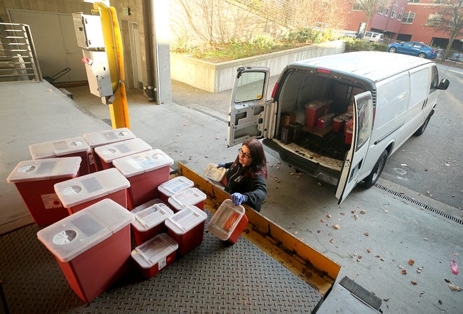 Lisa Al-Hakim, director of operations of the People's Harm Reduction Alliance, unloads used syringes at the Norm Dicks Government Center on Thursday. Some of Kitsap's city leaders are concerned that the county's syringe program is contributing to needles that are improperly disposed of.