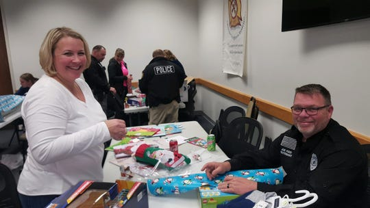 Lieutenant Joe Kidd and his wife Cortney help wrap presents in the training room at the Black Mountain Police Department on Dec. 4.