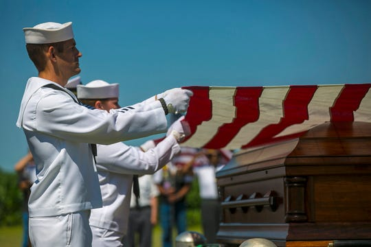 FILE - In this July 7, 2018 file photo, U.S. Navy sailors fold the U.S. flag draped over the casket with the remains of Seaman First Class Leon Arickx at Sacred Heart Cemetery in Osage, Iowa. Arickx' remains, which were unidentifiable after his death after the Japanese attack at Pearl Harbor in 1941, were identified through DNA testing earlier this year. More than three-quarters of a century after the devastating attack killed nearly 2,400 in Hawaii, the bodies of some sailors killed at Pearl Harbor are finally being laid to rest. (Chris Zoeller/Globe-Gazette via AP, File)