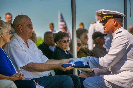 FILE - In this July 7, 2018 file photo, U.S. Navy Rear Admiral John Krietz presents a folded American flag to Mark Arickx, nephew to Seaman First Class Leon Arickx, at Sacred Heart Cemetery in Osage, Iowa. Arickx' remains, which were unidentifiable after his death after the attack at Pearl Harbor in 1941, were identified through DNA testing earlier this year. More than three-quarters of a century after the Japanese attack killed nearly 2,400 in Hawaii, the bodies of some sailors killed at Pearl Harbor are finally being laid to rest. (Chris Zoeller/Globe-Gazette via AP,File)
