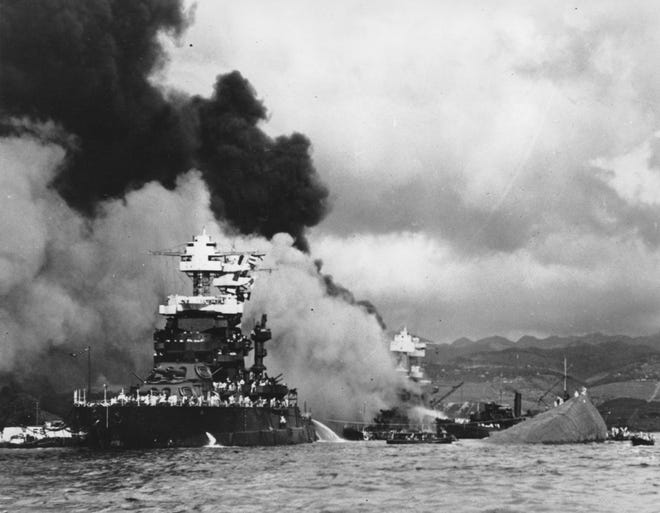 In this Dec. 7, 1941 file photo, part of the hull of the capsized USS Oklahoma is seen at right as the battleship USS West Virginia, center, begins to sink after suffering heavy damage. Two crewmen aboard the USS Oklahoma that day were recently identified through DNA analysis, including one sailor from Laramie, Wyoming.