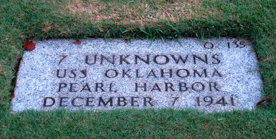 FILE - In this Dec. 5, 2012, file photo, the National Memorial Cemetery of the Pacific in Honolulu displays a gravestone identifying it as the resting place of seven unknown people from the USS Oklahoma who died in Japanese bombing of Pearl Harbor. More than 75 years after nearly 2,400 members of the U.S. military were killed in the Japanese attack at Pearl Harbor some who died on Dec. 7, 1941, are finally being laid to rest in cemeteries across the United States. After DNA allowed the men to be identified and returned home, their remains are being buried in places such as Traer, Iowa and Ontonagon, Michigan. (AP Photo/Audrey McAvoy, File)