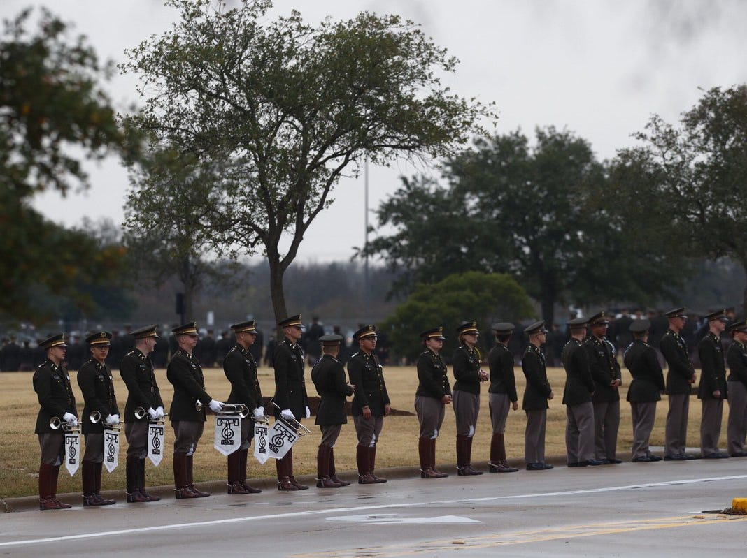 Texas A&M cadets line the street near the George Bush Presidential Library and Museum ahead of the arrival of the former president's casket on Thursday, Dec. 6, 2018, in College Station, Texas.