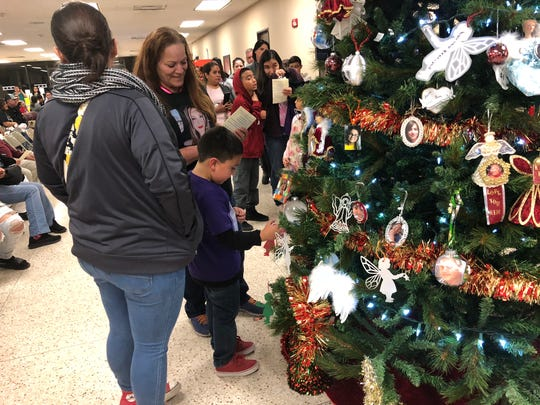 People hang ornaments at the 21st Annual Tree of Angels in Nueces County.
