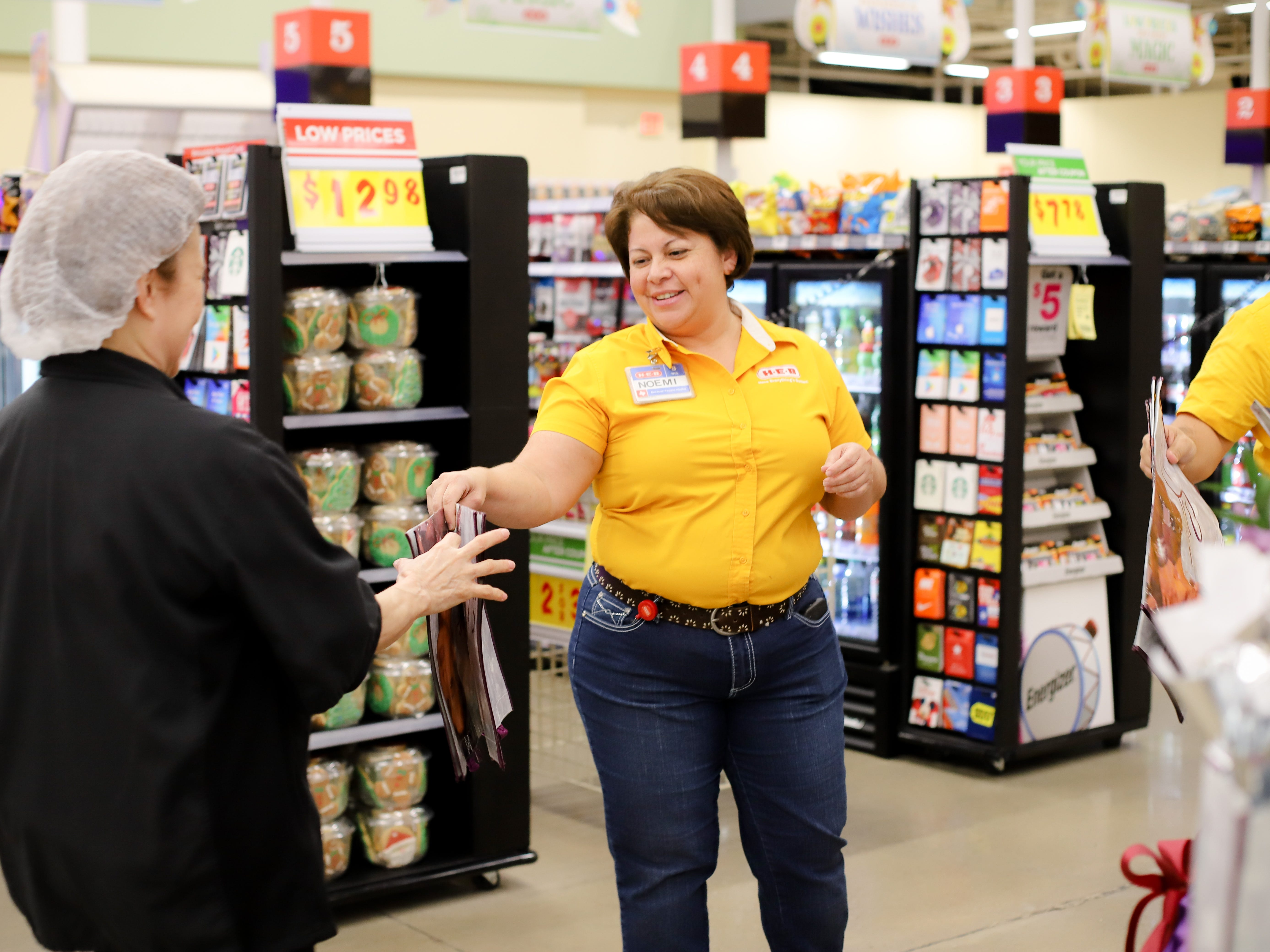 An H-E-B employee hands two Selena bags to a customer on Dec. 6, 2018.